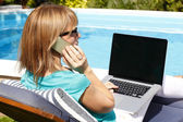 Woman at garden with phone and laptop — Stockfoto