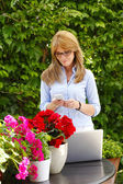 Beautiful mature florist with mobile — Stock Photo