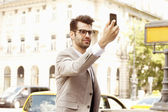 Businessman taking self portrait at the city — Stock Photo