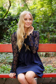 Blond woman sitting at park — Stock Photo