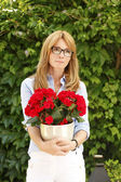 Mature woman holding flowers — Stock Photo