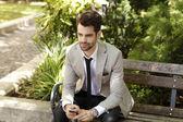 Modern businessman sitting in park — Stock Photo
