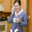 Woman in kitchen with coffee and phone — Stock Photo
