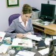 Woman in messy office - Foto Stock