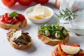 Bruschetta with beans and arugula, mushrooms, goat cheese — Stock Photo