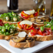 Bruschetta with beans and arugula, mushrooms, goat cheese — Stock Photo #38293645