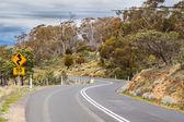 Camino sinuoso con advertencia de velocidad en tasmania — Foto de Stock