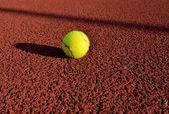 Bola de tênis em um tribunal. útil para desenhos de fundo de tênis. — Foto Stock