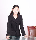 Oriental women, dressed in black casual dress, face serious, side tables and chairs, giving lectures — Stock Photo