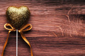 Valentine golden heart on wooden background. — Stock Photo