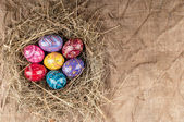 Colorful Easter eggs in nest from hay on textile background. — Stock Photo