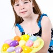 Young female child holding a plate of Easter eggs as if she is offering them to someone - Stockfoto