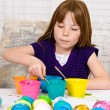 Young girl in the process of coloring Easter eggs has an egg on the spoon completely submerged in dye - 