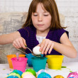 Young girl in the process of placing an Easter egg to be dyed on a spoon - Stock Photo