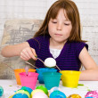 Young girl in the process of coloring Easter eggs beginning to lower an egg into the dye — Stock Photo