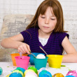 Young girl in the process of coloring Easter eggs has an egg on the spoon partially in the cup of dye — Stock Photo
