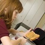 ung skolflicka förbereda en hälsosam lunch för skolan — Stockfoto