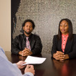 Young African American couple about to sign paperwork — Stock Photo #23258694
