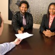 Stock Photo: Young African American couple about to sign paperwork