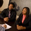Young African American couple about to sign paperwork — Stock Photo