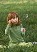 Young girl sitting in shady, green grass blowing bubbles — Stock Photo