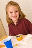 Young school girl eating a healthy lunch — Stock Photo