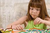 Young girl making bead bracelets — Stock Photo