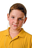 Young boy listening to MP3 player with earbuds in his ears — Stock Photo