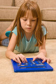 Young Caucasian female child works on an oversized calculator — Stock Photo