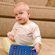 Young baby in pajamas with a large calculator - Stock Photo