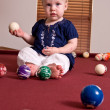 A young child sitting alone on a billiard table — Stock Photo #23904807