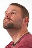 Un homme mal rasé caucasien en vue de profil, regardant vers le haut vers la gauche de l'appareil photo — Photo