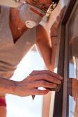 Mulher polimento uma janela com areia — Fotografia Stock