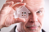 Man looking through a little house in front of you — Stock Photo