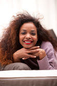 Beautiful afro-american woman happily relaxing lying on a sofa — Stockfoto