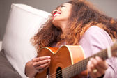 Beautiful afroamerican girl having fun playing guitar — Stock Photo