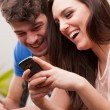 Man and woman having fun with their mobile phones — Stock Photo