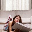 Young girl reading a big book on her living room — Stock Photo #51313633
