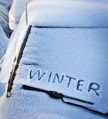 Winter written in snow on car windscreen below windscreen wiper — Stock Photo