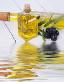 Oil and olives with water reflection — Stock Photo