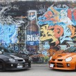 Graffiti covered wall with 2 SRT-4 cars — Stock Photo