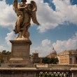 Statue of angel on bridge with St. Peter's Basilica on backgroun - Stock Photo