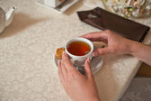 Cup of tea and hands. — Stock Photo