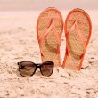 Sunglasses and flip-flops on a beach — Stock Photo