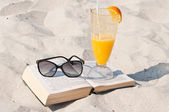 Book and sunglasses on a sand beach — 图库照片