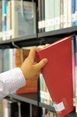 Closeup hand selecting book from a bookshelf — Stock Photo