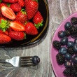 Two plates with strawberries and bilberries - 