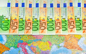Euro bills in a row on the map — Stock Photo