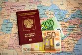 Passaporte com dinheiro no mapa — Fotografia Stock