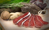 Sliced salami with herbs — Stock Photo
